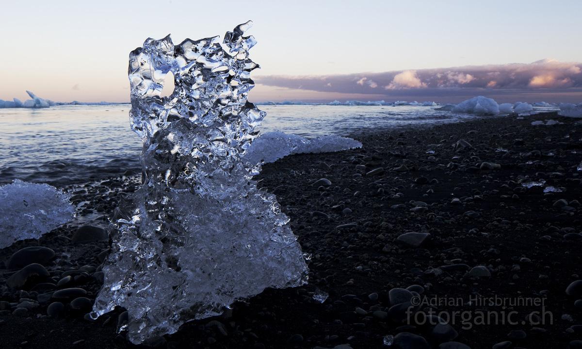 Eisberg am schwarzen Lavastrand von Jökulsárlón