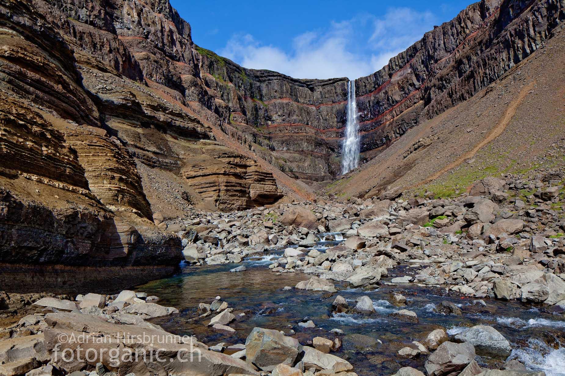 Die Schönheit des vierthöchsten Wasserfalls Islands liegt vor allem im leuchtend roten, lehmigen Sedimentgestein begründet.