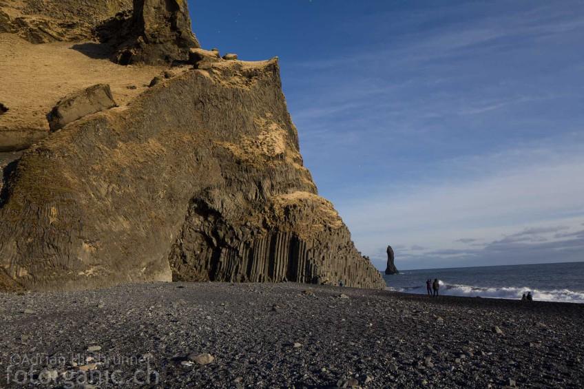 Der riesige Basaltsäulenfelsen von Vík í Mýrdal mit einer Felsnadel des Reynisdrangar im Hintergrund.