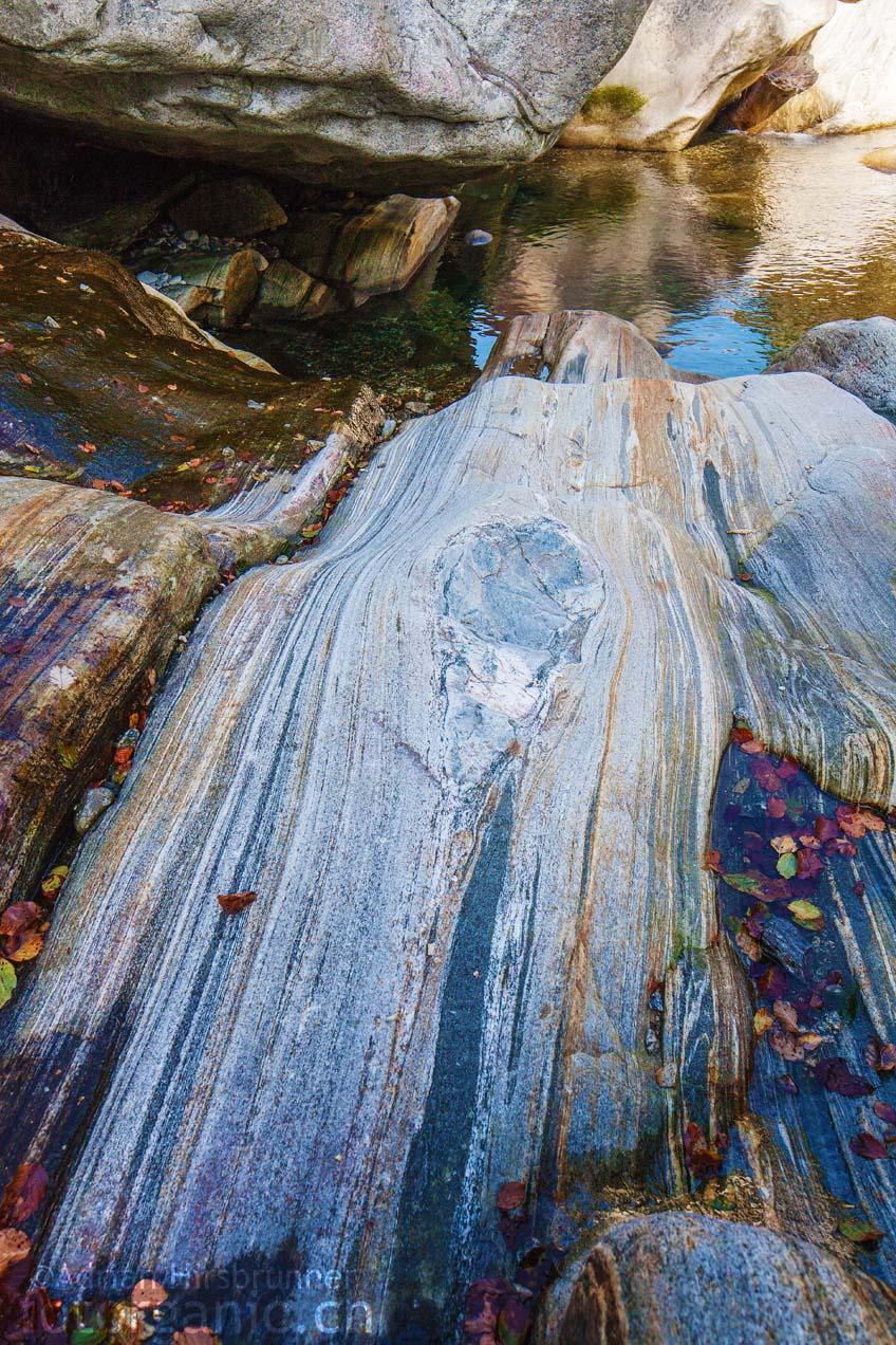 Wasserbecken und gebänderte Felsformationen.