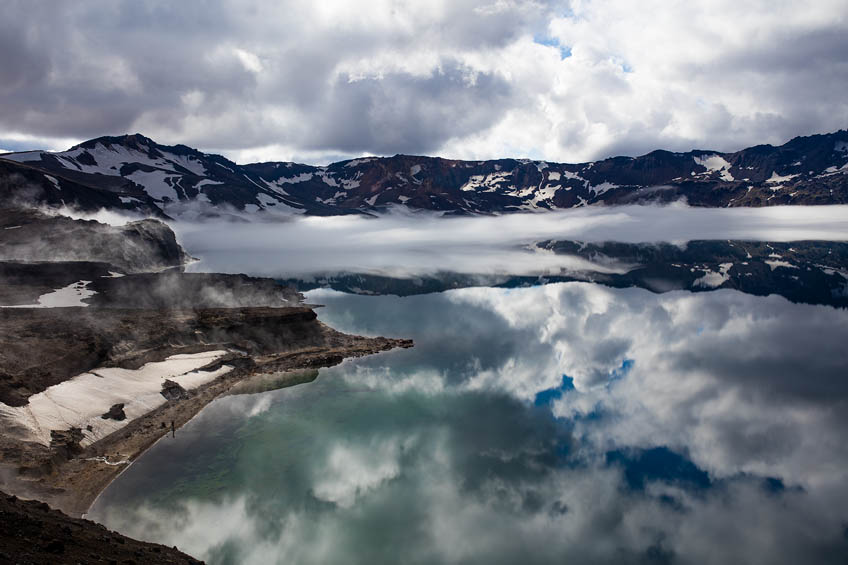 Der Östjuvatn mit Nebelbänken. Auf dem Grund des Calderasees sind Sinterungen auszumachen aus denen Blasen aufsteigen.