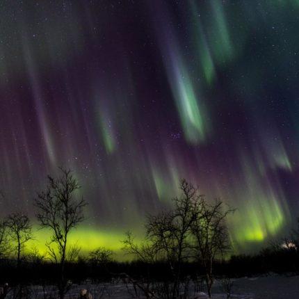 Wie ein Schauer mit glühenden Tropfen stehen die Polarlichter am Himmel.
