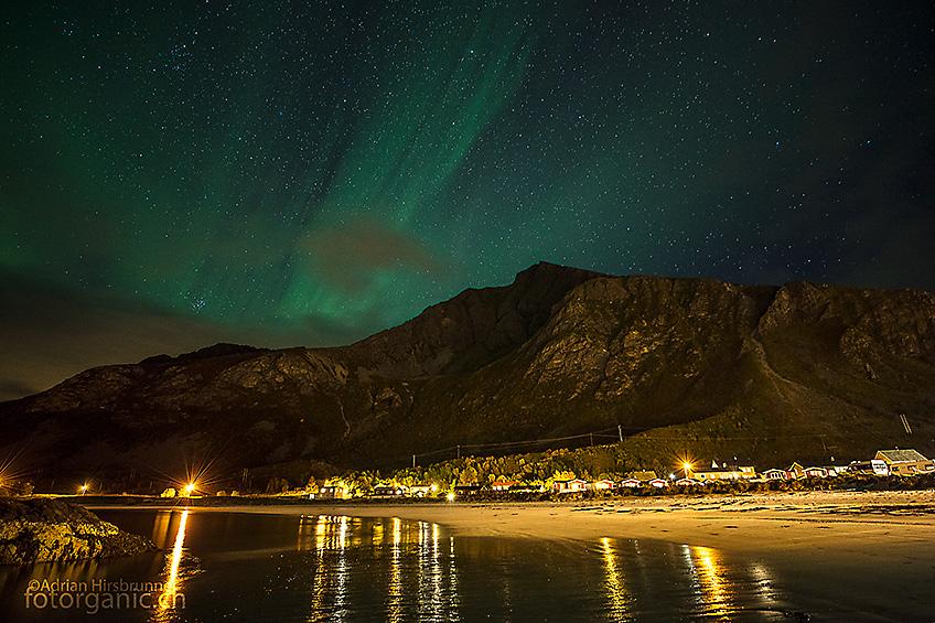 Ruhiges Nordlicht hat durchaus seinen Reiz. Grünes Leuchten am Strand von Ramberg.